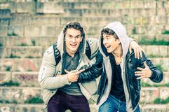 Young hipster brothers having fun with each other. Best friends sharing free time together in urban area outdoors - Handsome guys with winter fashion style Stock Photography