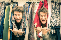 Young hipster brothers at the weekly cloth market - Best friends. Sharing free time having fun and shopping in the old town in a sunny day - Guys enjoying Royalty Free Stock Photos