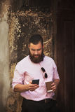 Young hipster businessman with beard holding  phone and a coffee Royalty Free Stock Photo