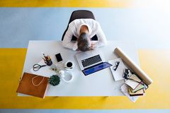Businessman at the desk with laptop in his office. Young hipster businessman in his office, sitting at the desk, having a break and resting Royalty Free Stock Image