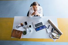 Businessman at the desk with laptop in his office. Young hipster businessman in his office, sitting at the desk, working, laptop in front of him Stock Images