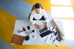 Businessman at the desk with laptop in his office. Young hipster businessman in his office, sitting at the desk, working, laptop in front of him. High angle Stock Image