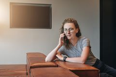A young hipster businesswoman talking on her cell phone.Telephone conversations.Girl is waiting for meeting with. A young hipster businesswoman in glasses is stock photos