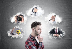 Young hipster buy considering career paths. Side view of a pensive bearded hipster guy standing near a blackboard with a career choice sketch on it Royalty Free Stock Photography