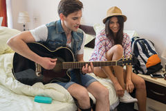 Young hipster couple in the bedroom preparing for vacation. Men is plating guitar. Woman is putting on her sneakers Royalty Free Stock Photography