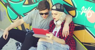 Young hipster couple browsing the internet. On a tablet computer as they relax in the street sitting in front of a colorful graffiti covered wall stock video footage