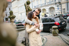 Young hipster couple  with coffee kissing, hugging in old town Stock Image