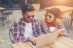 Young hipster couple drinking talking having fun laughing smiling happy outdoor at europe cafe style. stock images