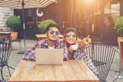 Young hipster couple drinking talking having fun laughing smiling happy outdoor at europe cafe style. stock photo