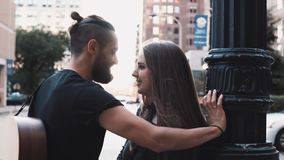 Young hipster couple flirt in the street. Romantic Caucasian man and woman talk smiling, kissing outside. 4K. Dating. stock footage