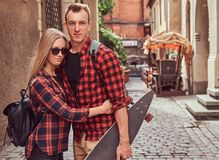 Young hipster couple, handsome skater and his girlfriend cuddling while standing on the old Europe street. Young hipster couple, handsome skater and his Stock Photography
