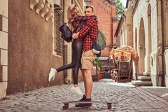 Young hipster couple, handsome skater and his girlfriend cuddling while standing on the old narrow streets of Europe. Young hipster couple, handsome skater and stock photo