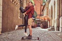 Young hipster couple, handsome skater and his girlfriend cuddling while standing on the old narrow streets of Europe. Young hipster couple, handsome skater and stock photography