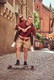 Young hipster couple, handsome skater and his girlfriend have fun while walking on the old narrow street of Europe. Young hipster couple, handsome skater and stock image