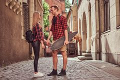 Young hipster couple, handsome skater and his girlfriend standing on old narrow streets of Europe. Young hipster couple, handsome skater and his girlfriend stock image