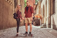 Young hipster couple, handsome skater and his girlfriend standing on old narrow streets of Europe. Young hipster couple, handsome skater and his girlfriend stock photography