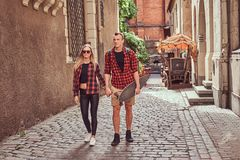 Young hipster couple, handsome skater and his girlfriend walking around an old narrow streets of Europe. Young hipster couple, handsome skater and his royalty free stock photo