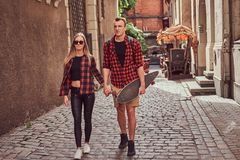 Young hipster couple, handsome skater and his girlfriend walking around an old narrow streets of Europe. Young hipster couple, handsome skater and his stock image