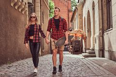 Young hipster couple, handsome skater and his girlfriend walking around an old narrow streets of Europe. Young hipster couple, handsome skater and his stock photography
