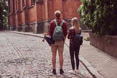 Young hipster couple, handsome skater and his girlfriend walking around an old streets of Europe. Young hipster couple, handsome skater and his girlfriend royalty free stock photos