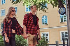 Young hipster couple, handsome skater and his girlfriend walking around an old streets of Europe. Young hipster couple, handsome skater and his girlfriend royalty free stock image