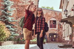 Young hipster couple, handsome skater and his girlfriend walking around an old streets of Europe. Young hipster couple, handsome skater and his girlfriend stock image