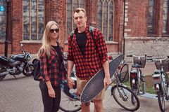 Young hipster couple, handsome skater and his girlfriend walking around an old streets of Europe. Young hipster couple, handsome skater and his girlfriend royalty free stock images