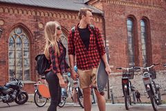 Young hipster couple, handsome skater and his girlfriend walking around an old streets of Europe. Young hipster couple, handsome skater and his girlfriend stock photo