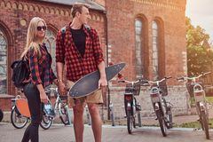 Young hipster couple, handsome skater and his girlfriend walking around an old streets of Europe. Young hipster couple, handsome skater and his girlfriend royalty free stock photography