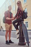 Young hipster couple, handsome skater holding hands his girlfriend who sitting on a fire hydrant in an old Europe street. Young hipster couple, handsome skater Royalty Free Stock Photography