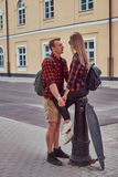 Young hipster couple, handsome skater holding hands his girlfriend who sitting on a fire hydrant in an old Europe street. Young hipster couple, handsome skater Royalty Free Stock Images