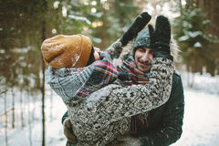 Young hipster couple having fun in winter forest Royalty Free Stock Images