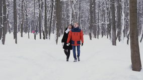 Young hipster couple having a walk in winter forest in slowmotion stock footage