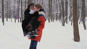 Young hipster couple having a walk in winter forest in slowmotion stock video