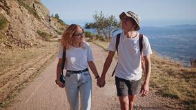 Young hipster couple hikes on mountain road on sunset. Frontal view on beautiful couple wearing white tshirts, adventure clothing, holding hands and walking on stock video footage