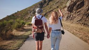 Young hipster couple hikes on mountain road on sunset. Pretty beautiful people, in trendy outfits, hipster backpack and camera, they hold hands and look around stock footage