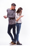 Young hipster couple ignoring each other using their smart-phones. He look at her phone. Stock Image