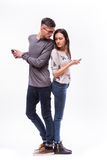 Young hipster couple ignoring esch other using their smart-phones. He look at her phone. Royalty Free Stock Images