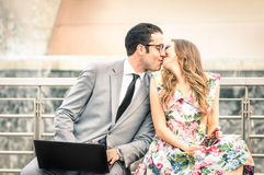 Young hipster couple kiss and sit with laptop and smartphone Royalty Free Stock Image