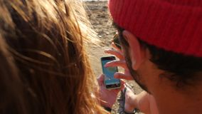 Young hipster couple looking for gps direction with smartphone on the beach. HD slow motion close up lifestyle footage. stock footage