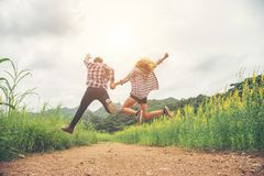 Young hipster couple in love outdoor jumping at yellow flower field with mountain sunset background. Jump up high enjoying. Freedom and enjoy royalty free stock photo