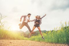 Young hipster couple in love outdoor jumping at yellow flower field with mountain sunset background. Jump up high enjoying. Freedom and enjoy stock photos