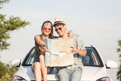 Beautiful young couple holding map outdoors. Road trip summer vacation concept. Young hipster couple sitting on car hood and looking at map. Travel on the road royalty free stock photo