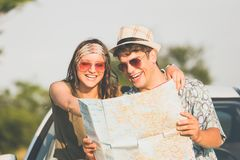 Beautiful young couple holding map outdoors. Road trip summer vacation concept. Young hipster couple sitting on car hood and looking at map. Travel on the road royalty free stock images