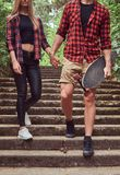 Young hipster couple, walk in a park, holding hands, descending the stairs. Royalty Free Stock Images