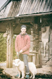 Young hipster with dog in front of wooden house Royalty Free Stock Photo