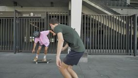 Young hipster is doing skateboard trick in daytime in summer, man with camera is following him and doing video, sport