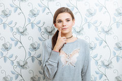 Young hipster dreamy woman posing against wall with vintage wallpapers pattern Stock Image