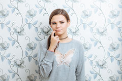 Young hipster dreamy woman posing against wall with vintage wallpapers pattern Stock Images