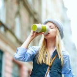 Young hipster enjoying cup of hot beverage in the city Royalty Free Stock Images